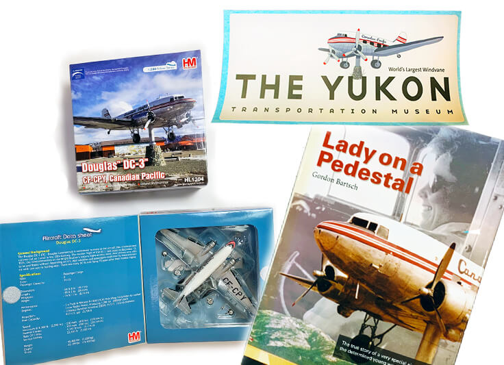 product display: DC-3 CPY scale model, DC-3 bumper sticker, Lady on a Pedestal book