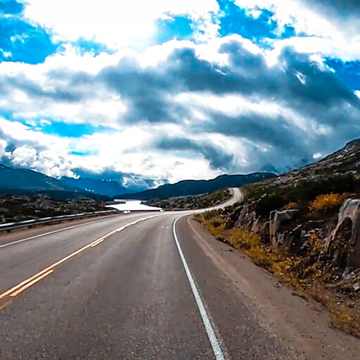 Looking down the South Klondike Highway with a bright blur sky and bright energetic clouds